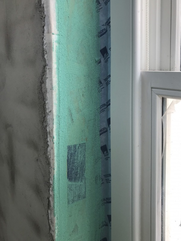 Aquabond painted over the the smooth surface around a window frame.