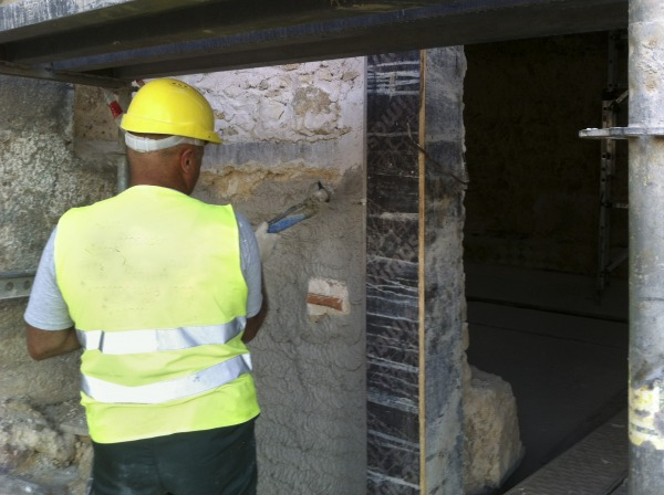 Diathonite Regularisation being spray applied to outer masonry wall