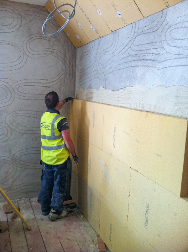 Gutex Thermoroom boards being tapped to ensure the boards are firmly adhered onto the wall.