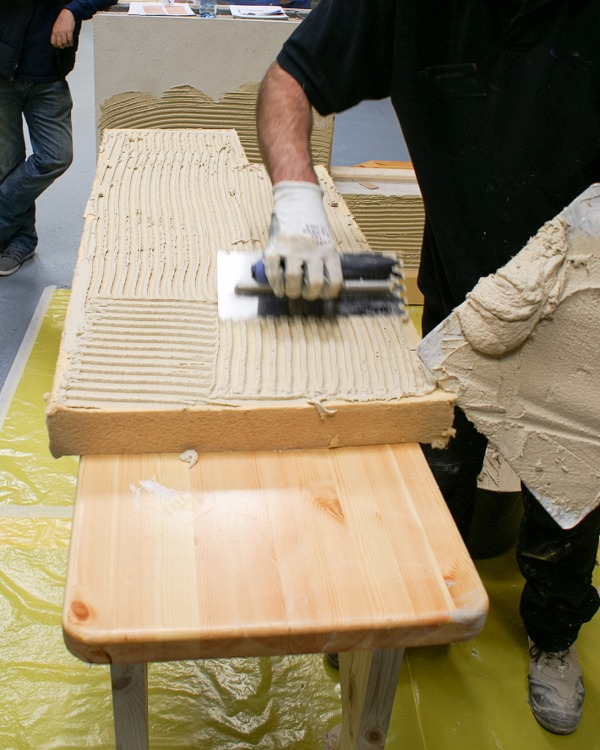 Thermoroom adhesive being applied to a Thermoroom board with an hand trowel