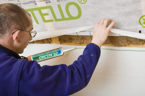 Orcon F sticking a sheet of Intello Plus to an internal wall.