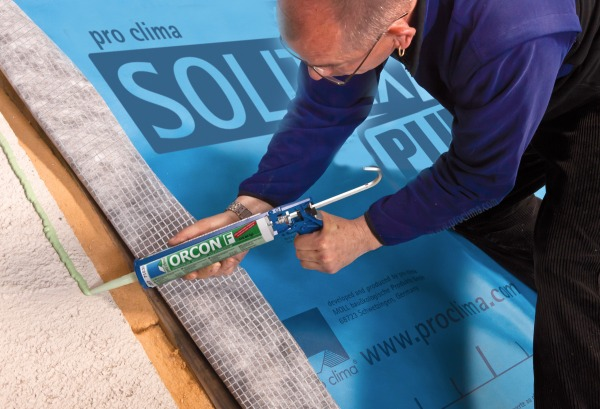 Orcon F being applied on an external wall underneath a sheet of Solitex Plus.
